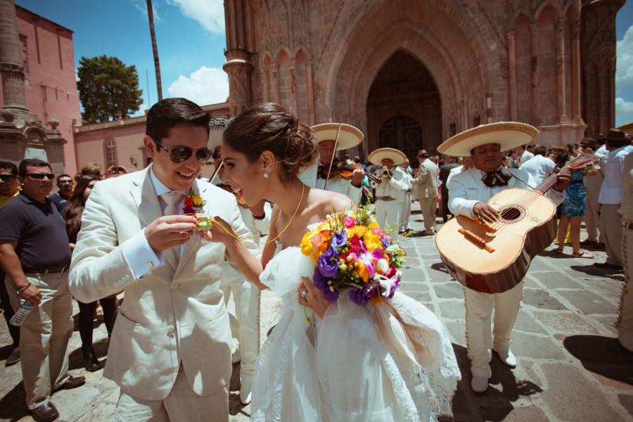 los novios celebran con tequila afuera de la Parroquia de San Miguel Arcángel