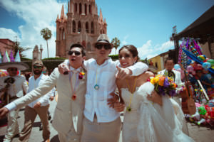 amigo celebra con los novios afuera de la Parroquia de San Miguel Arcángel