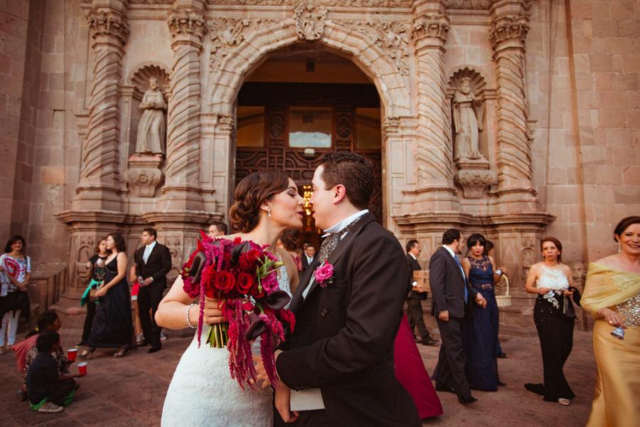 foto del beso de los novios afuera de la iglesia